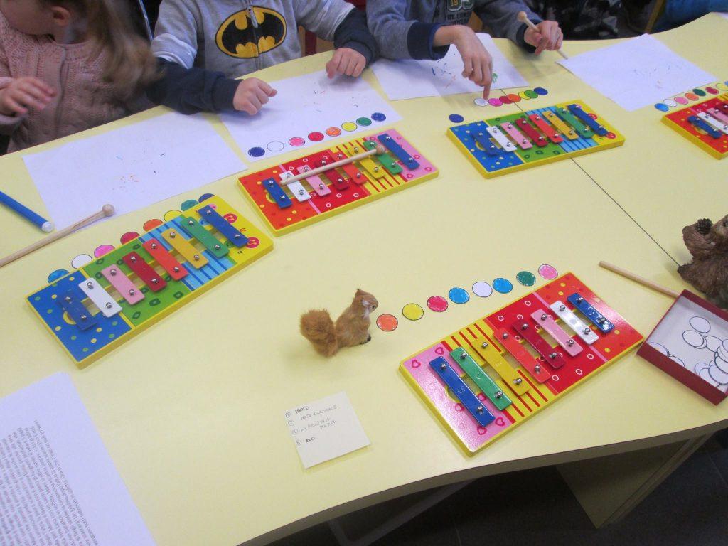 mani di bambini che suonano metallofoni colorati