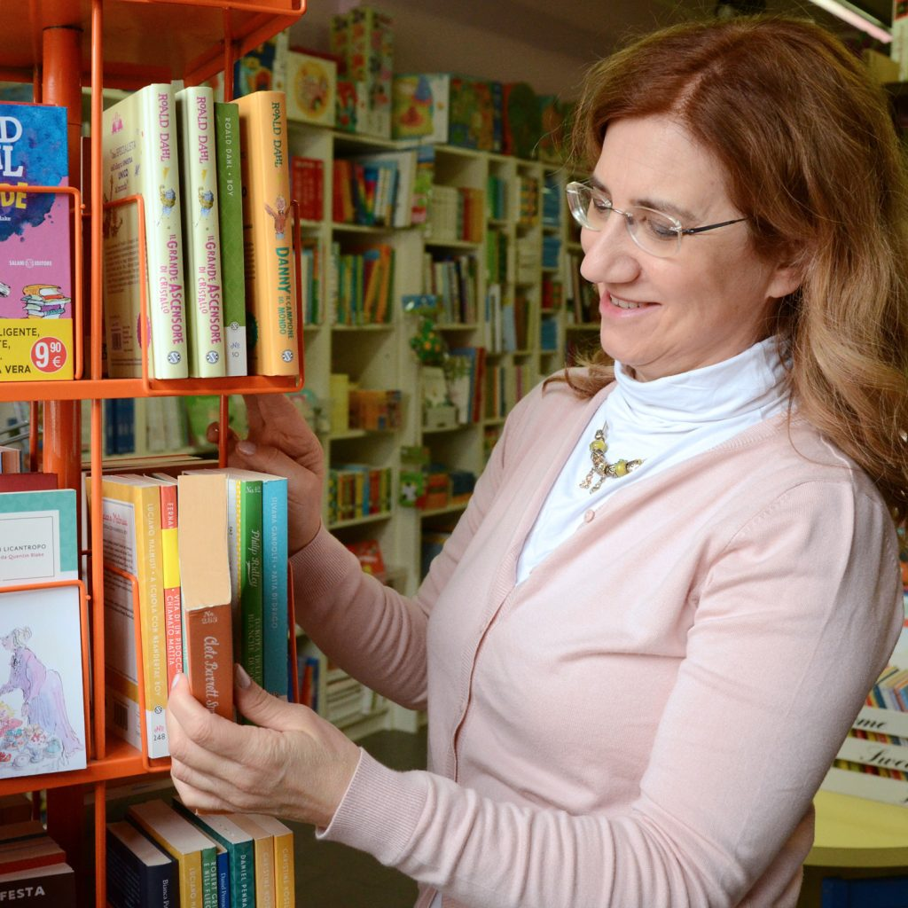 donna che sistema libri su scaffali di una libreria